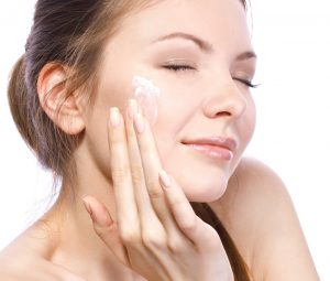 attractive woman applying face cream isolated on white